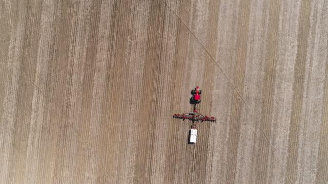 vídeos de stock, filmes e b-roll de trator arando e fertilizando os campos agrícolas na primavera próxima lyndon township, illinois, eua. vídeo aéreo de drone com o movimento da câmera panorâmica seguindo o trator. - illinois