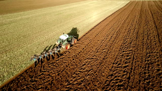 AERIAL : Tractor plowing Field