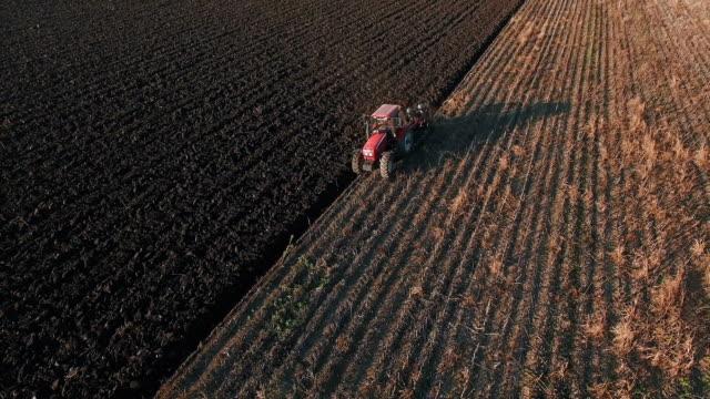 vídeos de stock, filmes e b-roll de trator a aragem em uma fazenda field - soil