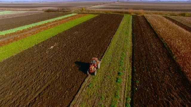 Tractor plowing on a rural farm land aerial