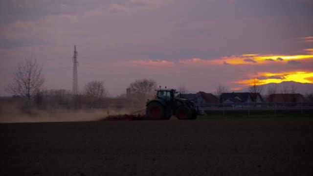 vidéos et rushes de ts tracteur labourage le domaine au coucher du soleil - tracteur