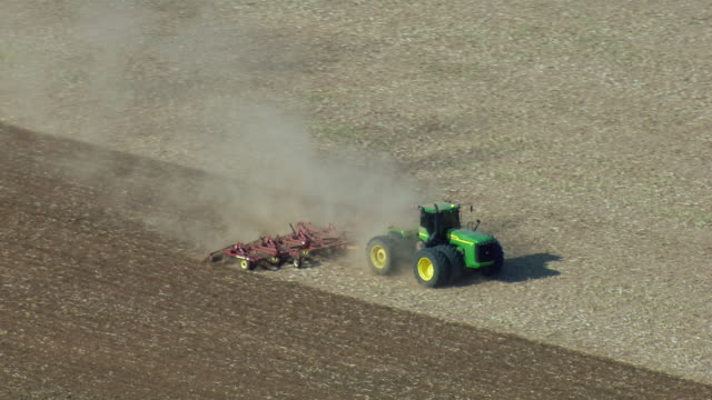 tractor plows field in oklahoma - pflug stock-videos und b-roll-filmmaterial
