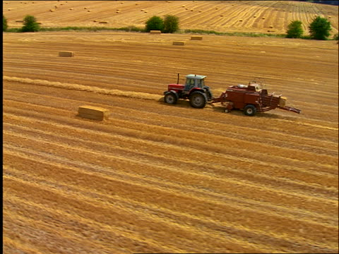 AERIAL tractor pulling hay baler in golden field / Oxfordshire, England