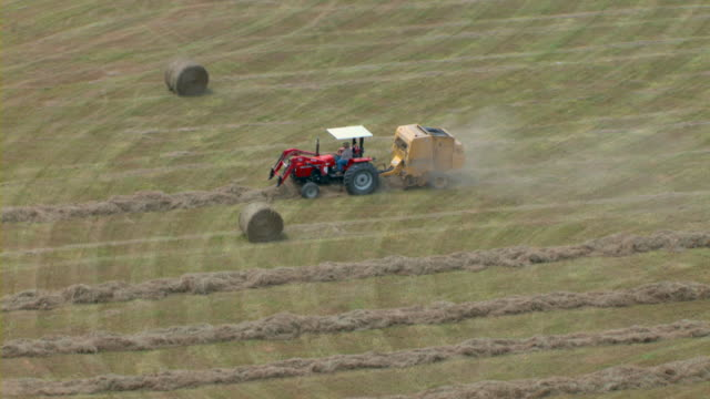 a tractor pulls a hay baler behind it through a field. - hay baler stock videos & royalty-free footage