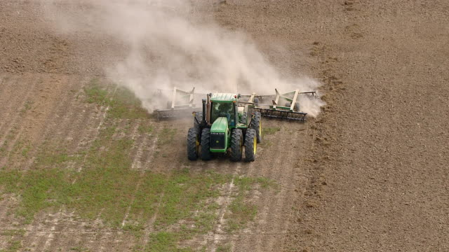 a tractor pulls a plow through a dirt field. - plough stock videos & royalty-free footage