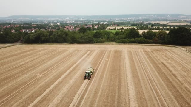 A tractor pulls a square baler press and creates square bales from the straw of a harvested wheat field for sprinkling and feeding the cattle stables...
