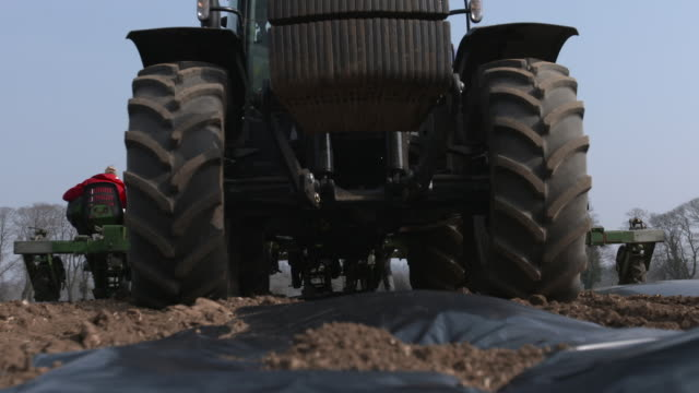 tractor pulls planting machine across field, uk - low angle view stock videos & royalty-free footage