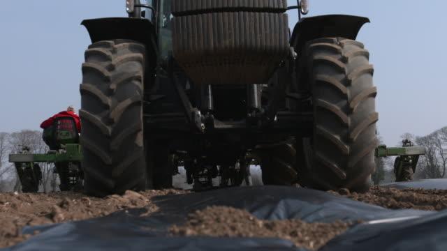 vidéos et rushes de tractor pulls planting machine across field, uk - tracteur