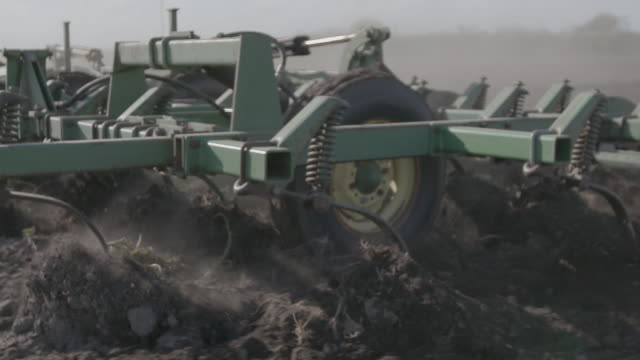 tractor pulls plow through dirt in slow motion, close-up - agricultural machinery stock videos & royalty-free footage