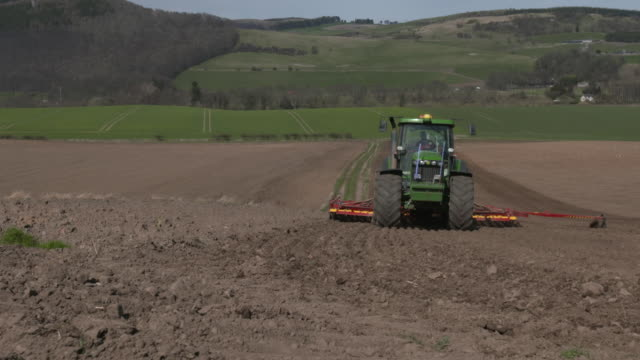 tl tractor pulls seed planting machine across field, uk - seed stock videos & royalty-free footage