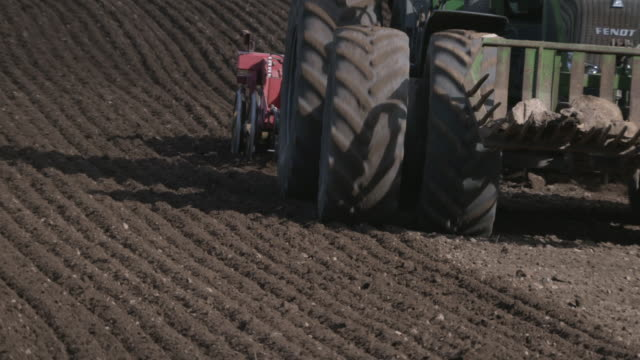 tractor pulls tilling machine across field, uk - tractor stock videos & royalty-free footage