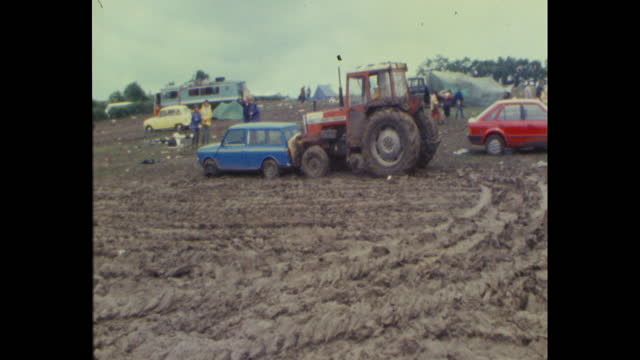 tractor pushes mini cooper car out of the mud as people leave worthy farm in pilton, somerset, after the 1985 glastonbury festival - tractor stock videos & royalty-free footage