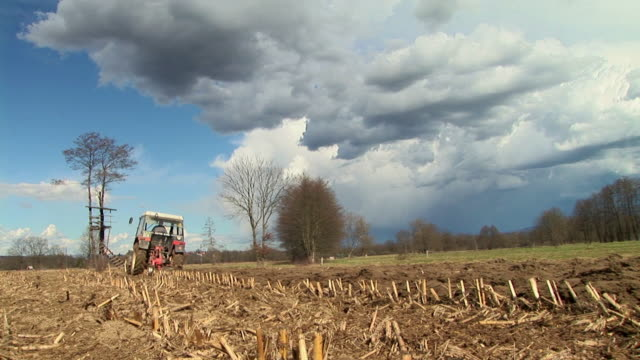 LA WS Tractor riding on field and preparing land for farming in Ljubljansko Barje / Notranjska, Slovenia