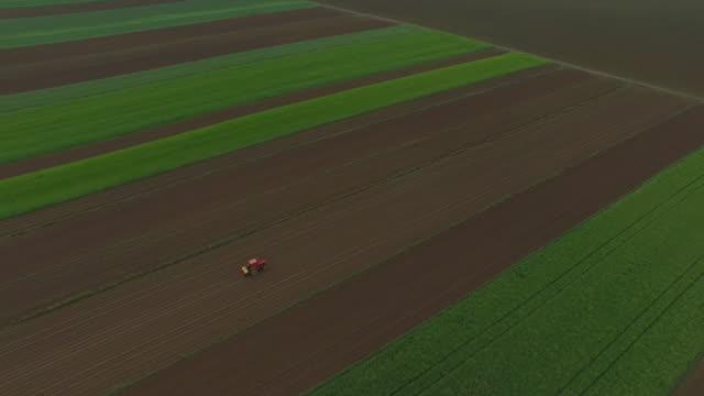 vídeos de stock, filmes e b-roll de trator aérea jogando um campo - pulverizando