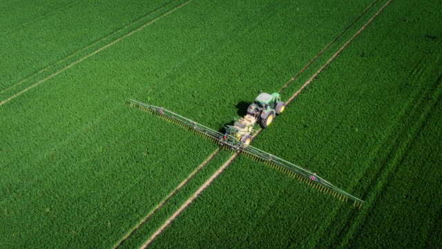 AERIAL: Tractor spraying chemicals