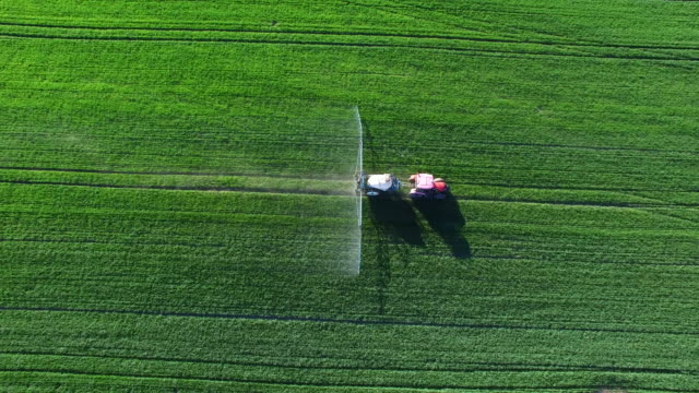 tractor spraying crop field in spring flyover - agriculture stock videos & royalty-free footage