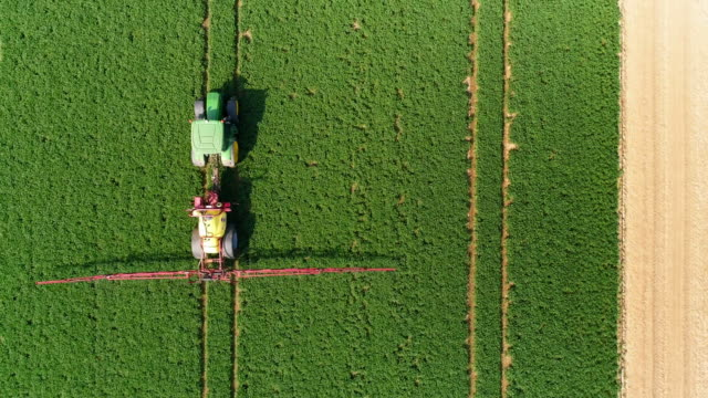 tractor spraying crop field in spring flyover - tractor stock videos & royalty-free footage
