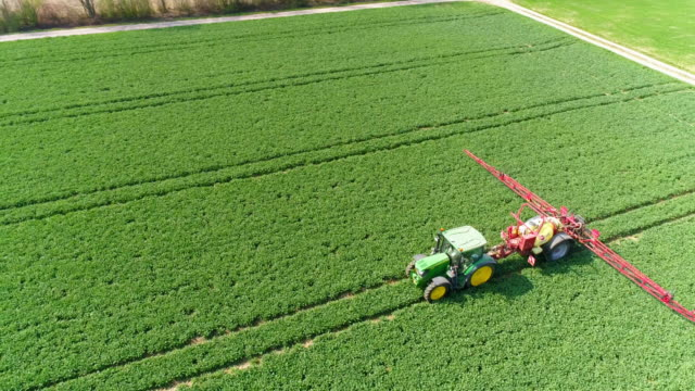 Tractor Spraying Crop Field In Spring