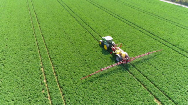 tractor spraying crop in spring flyover - insecticide stock videos & royalty-free footage