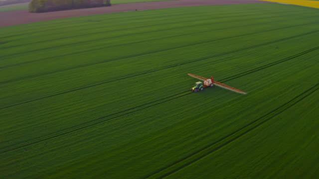ws aerial pov tractor spraying crop - tractor stock videos & royalty-free footage