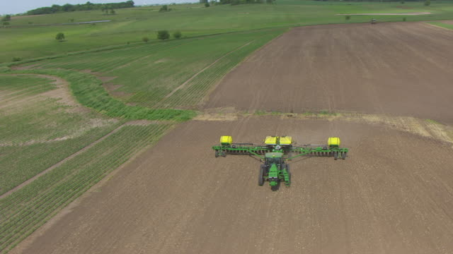 WS AERIAL POV Tractor spraying in farmland / Iowa County, Iowa, United States