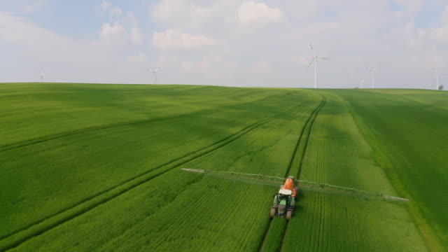 vídeos de stock e filmes b-roll de aerial tractor spraying pesticides on a field surrounded with wind turbines - sustainable resources
