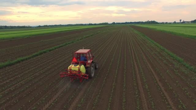 vídeos de stock e filmes b-roll de trator aéreo de pulverização de pesticidas em um campo - trator