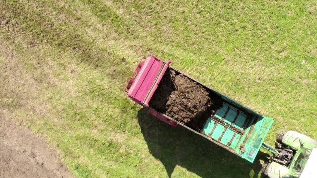 AERIAL Tractor spreading manure over the hrass