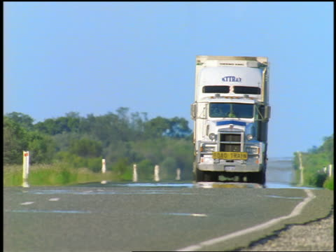 Tractor trailer driving thru heat wave on road past camera / Barrier Highway, NSW, Australia