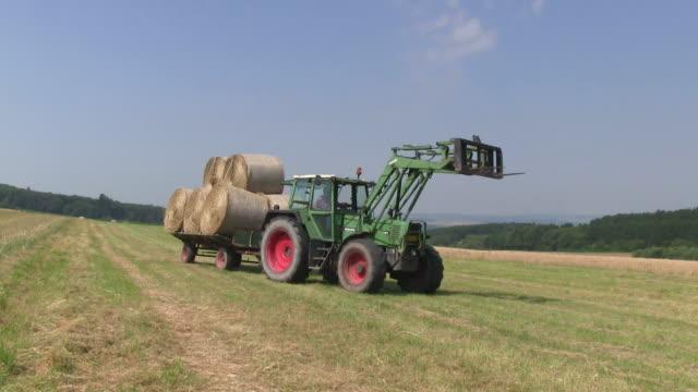 ms tractor transports bales of straw on field / saarburg, rhineland palatinate, germany - 干し草点の映像素材/bロール