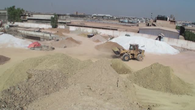 A tractor travels between piles of different varieties of clay in a preparation unit at the Shabbir Tiles Ceramics Ltd production facility in Karachi...