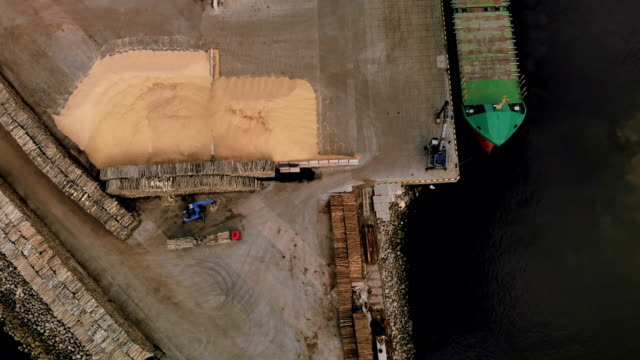 tractor unloads timber wood form truck near log piles at port with nautical vessel waiting - nautical vessel点の映像素材/bロール