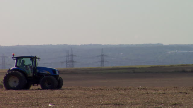 ws tractor with harrow crossing ploughed field, rochester, kent, united kingdom - harrow stock videos & royalty-free footage