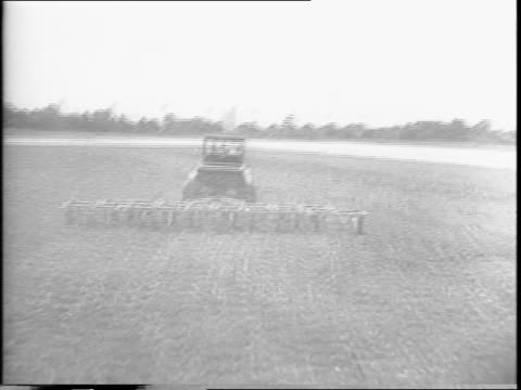 Tractor with nine mowers replaces single manual mower at Mitchel Field Air Force Base / ground view of sergeant using manual push mower / sergeant...