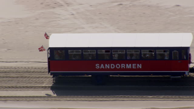 ms aerial ts zo tractor with passenger trolley on beach / nordjylland, denmark - western script stock videos & royalty-free footage