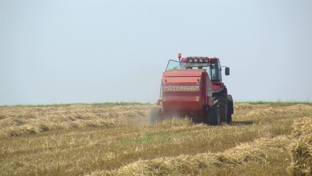 ms tractor with straw baler on harvested field / saarburg, rhineland palatinate, germany - 干し草点の映像素材/bロール
