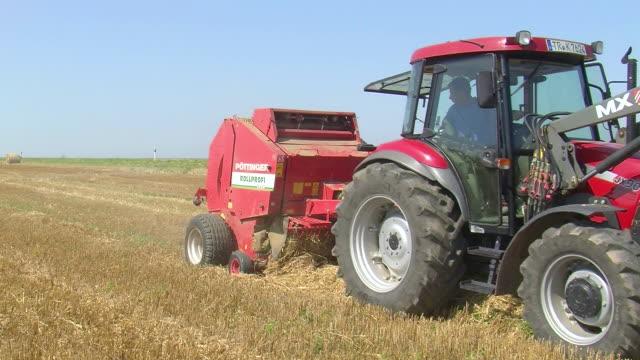 ms pan tractor with straw baler on harvested field / saarburg, rhineland palatinate, germany - hay baler stock videos & royalty-free footage