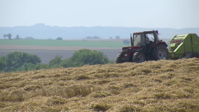 ms tractor with straw baler on harvested field / saarburg, rhineland palatinate, germany - hay baler stock videos & royalty-free footage