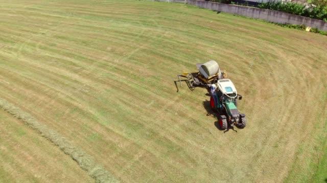 traktor wickelt einen heuballen in kunststoff - cereal plant stock-videos und b-roll-filmmaterial