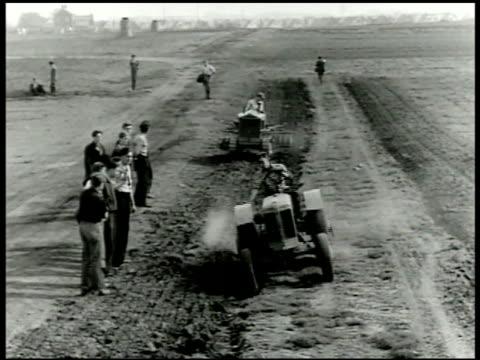 vídeos de stock e filmes b-roll de tractors making furrows on open land w/ adult males standing watching young adult males plowing open land w/ two horse team wwii - crise mundial de alimentos