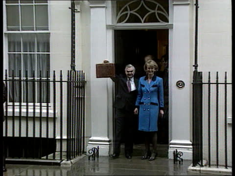 trade figures worsen england london downing st lms norman lamont mp coming out of no11 holding budget box accompanied by wife rosemary zoom in - budget stock-videos und b-roll-filmmaterial