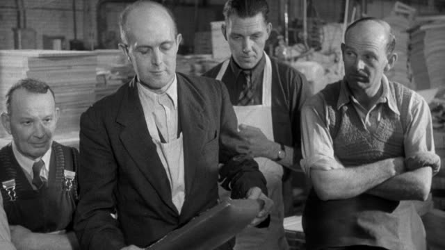 1955 MONTAGE Trade union workers attending a factory meeting where a complaint is discussed / United Kingdom