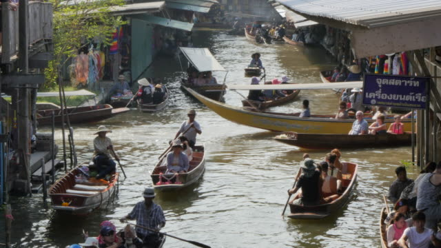 traders and buyers on boats at damnoen saduak floating markets, bangkok, thailand, southeast asia, asia - bangkok bildbanksvideor och videomaterial från bakom kulisserna