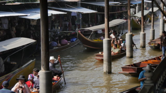 traders and buyers on boats at damnoen saduak floating markets, bangkok, thailand, southeast asia, asia - three quarter length stock videos & royalty-free footage