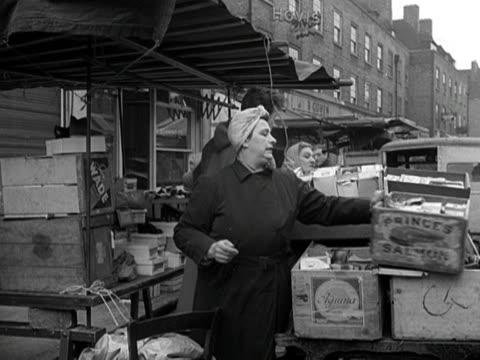 traders prepare their stalls for business at petticoat lane market - mercato all'aperto video stock e b–roll