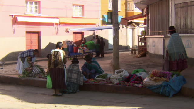 vidéos et rushes de traders selling fresh vegetables in small square, cart passes stacked with meat, copacabana, bolivia - vendre