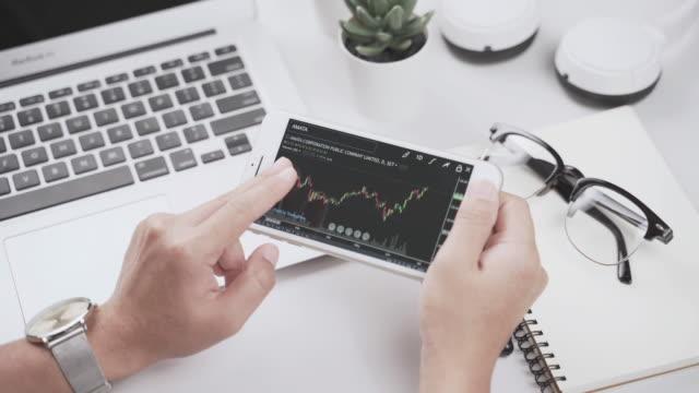 vídeos de stock, filmes e b-roll de mercado de ações de negociação no smartphone - casa de câmbio