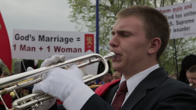 Tradition Family and Property marching band plays in front of a sign supporting a traditional definition of marriage People hold signs and crosses as...