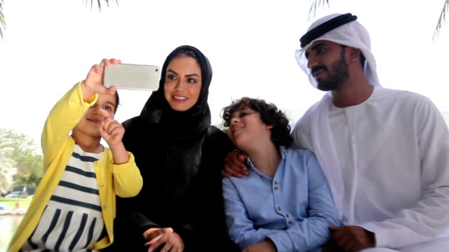 Traditional Arabian family taking selfie at nature
