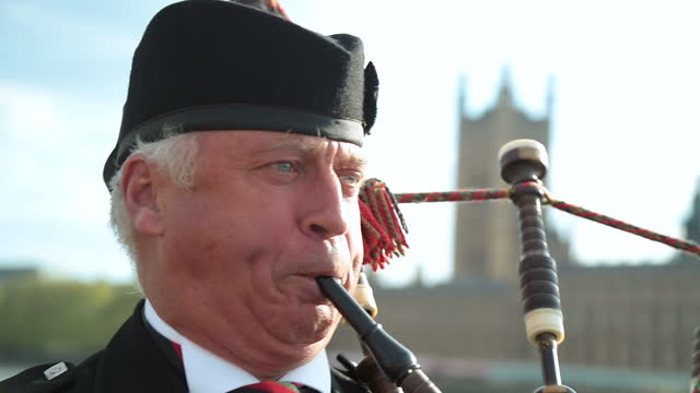 cu. traditional bagpipe player performs on westminster bridge in london. - house of commons stock videos & royalty-free footage
